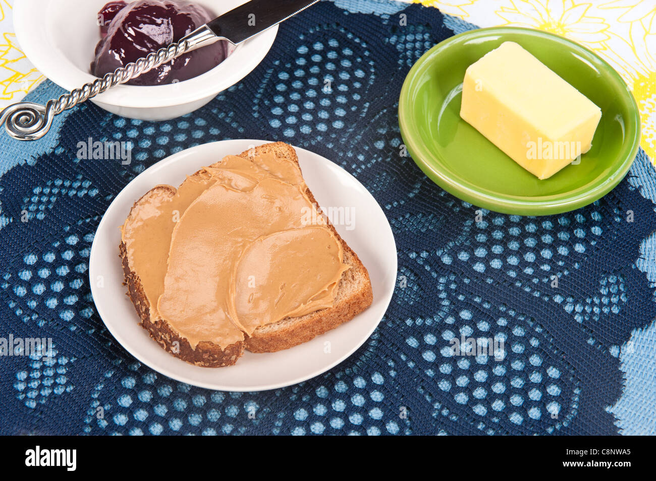 A setting of a peanut butter sandwich with jelly and butter - Stock Image
