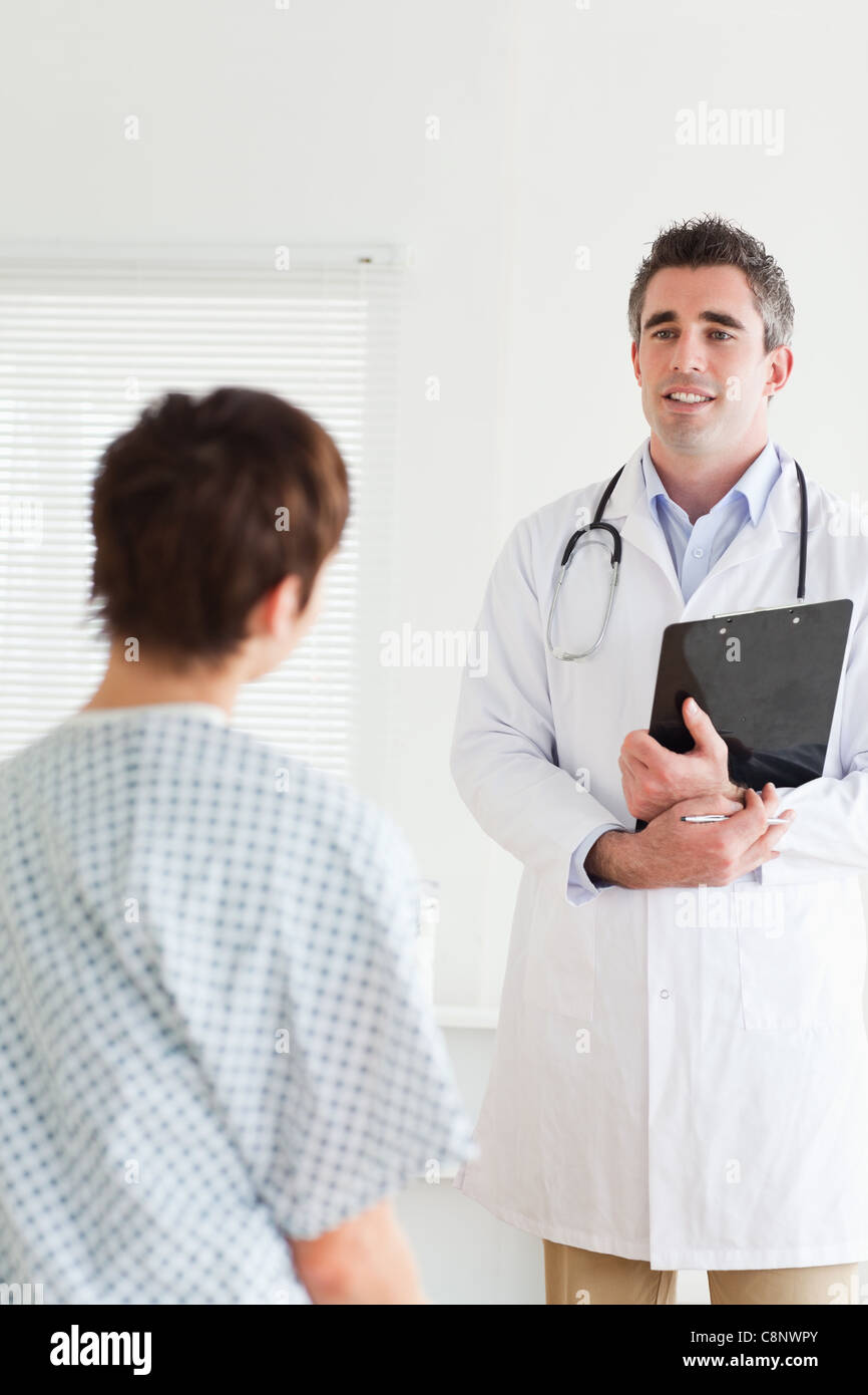 Doctor talking to a cute woman in hospital gown Stock Photo ...