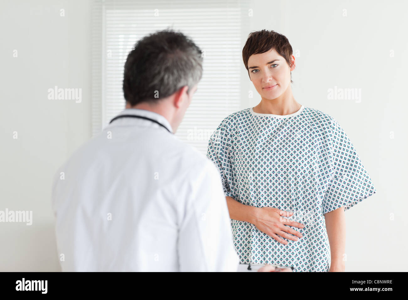 Brunette Woman in hospital gown talking to her doctor Stock Photo ...