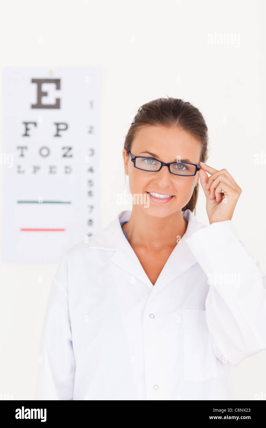 Eye specialist wearing glasses looking into the camera - Stock Image