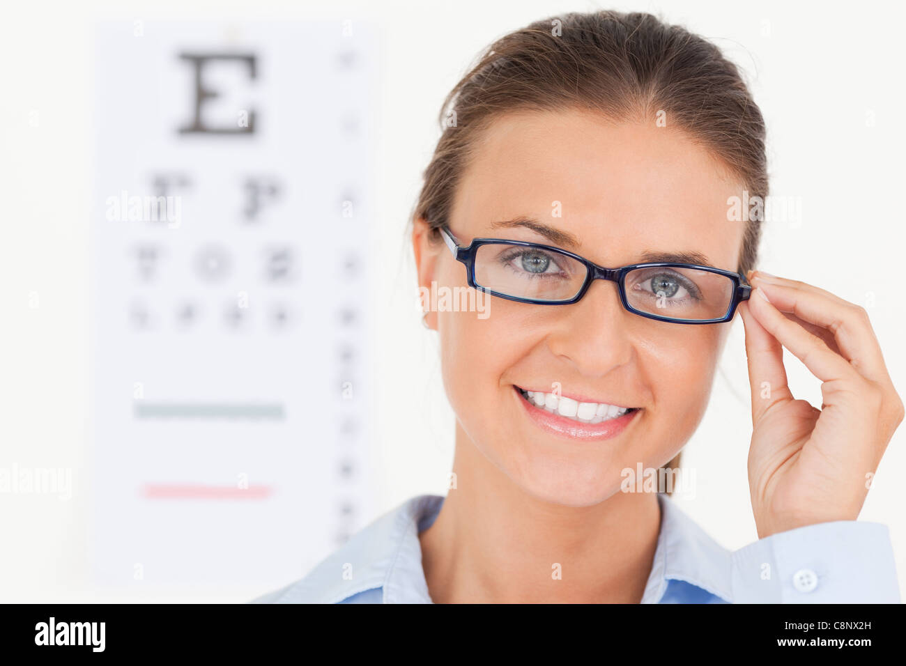 Close up of a good looking brunette eye specialist wearing glasses looking into the camera - Stock Image