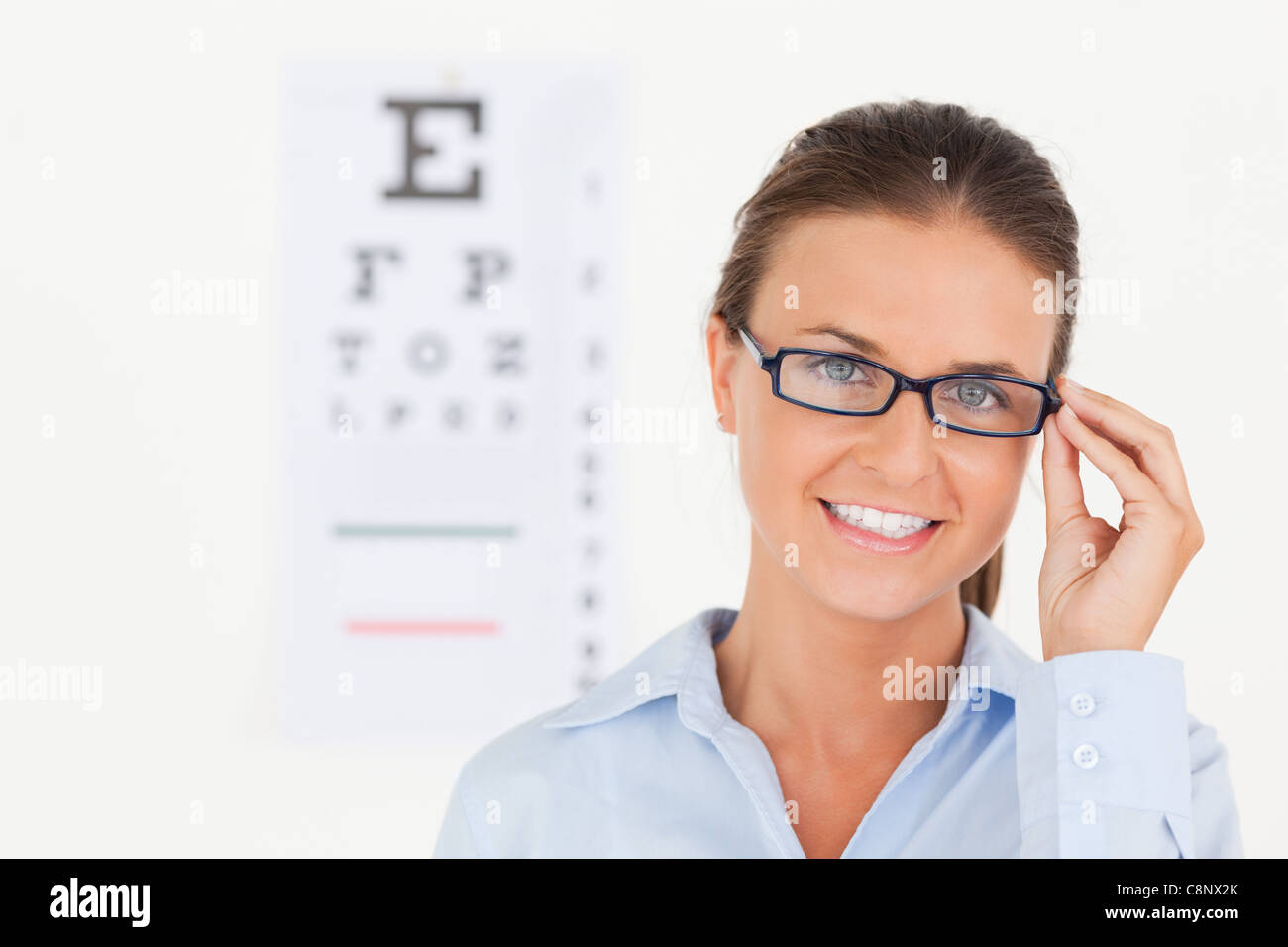 Close up of abrunette eye specialist wearing glasses looking into the camera - Stock Image