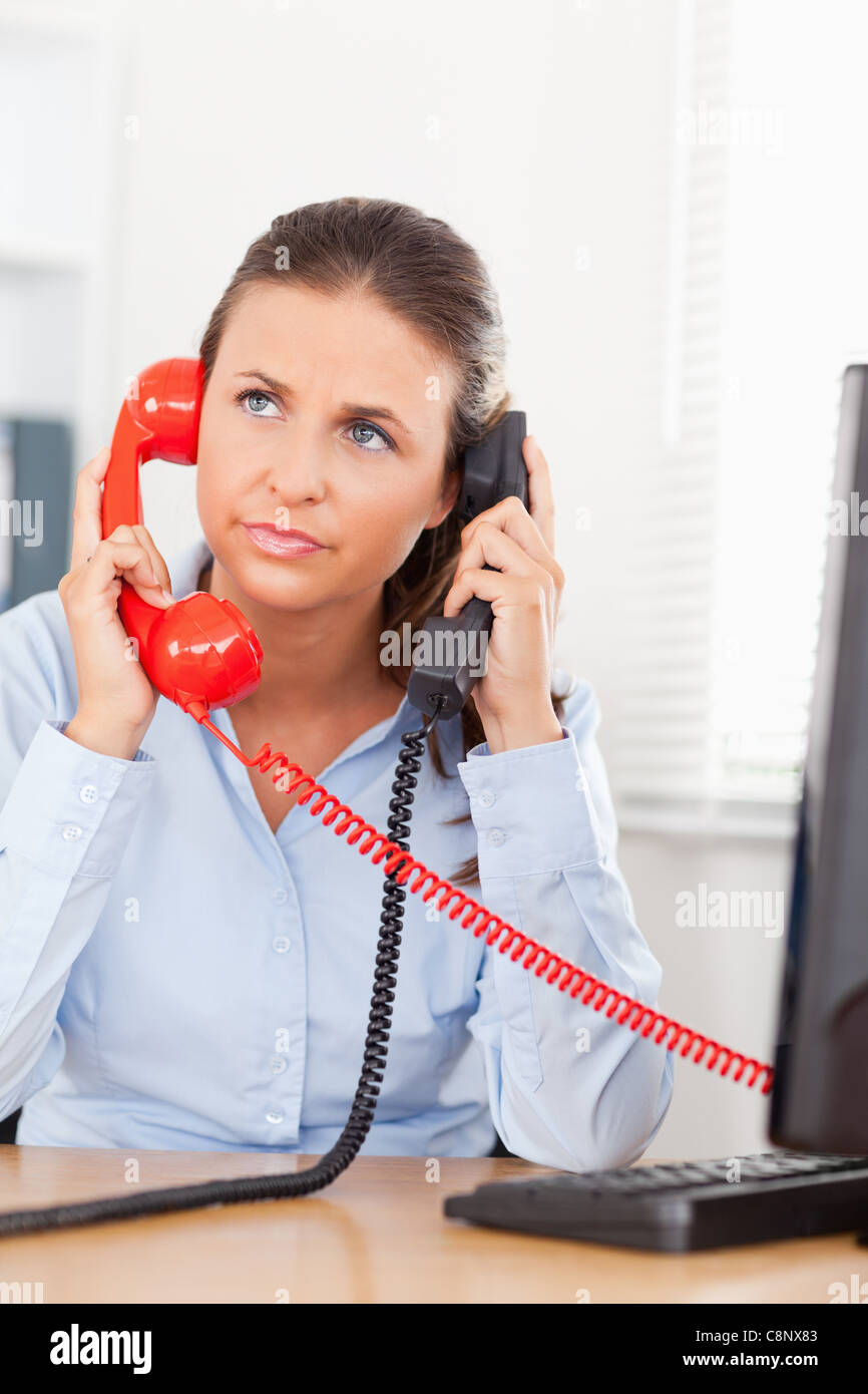 Businesswoman telephoning with two telephones - Stock Image