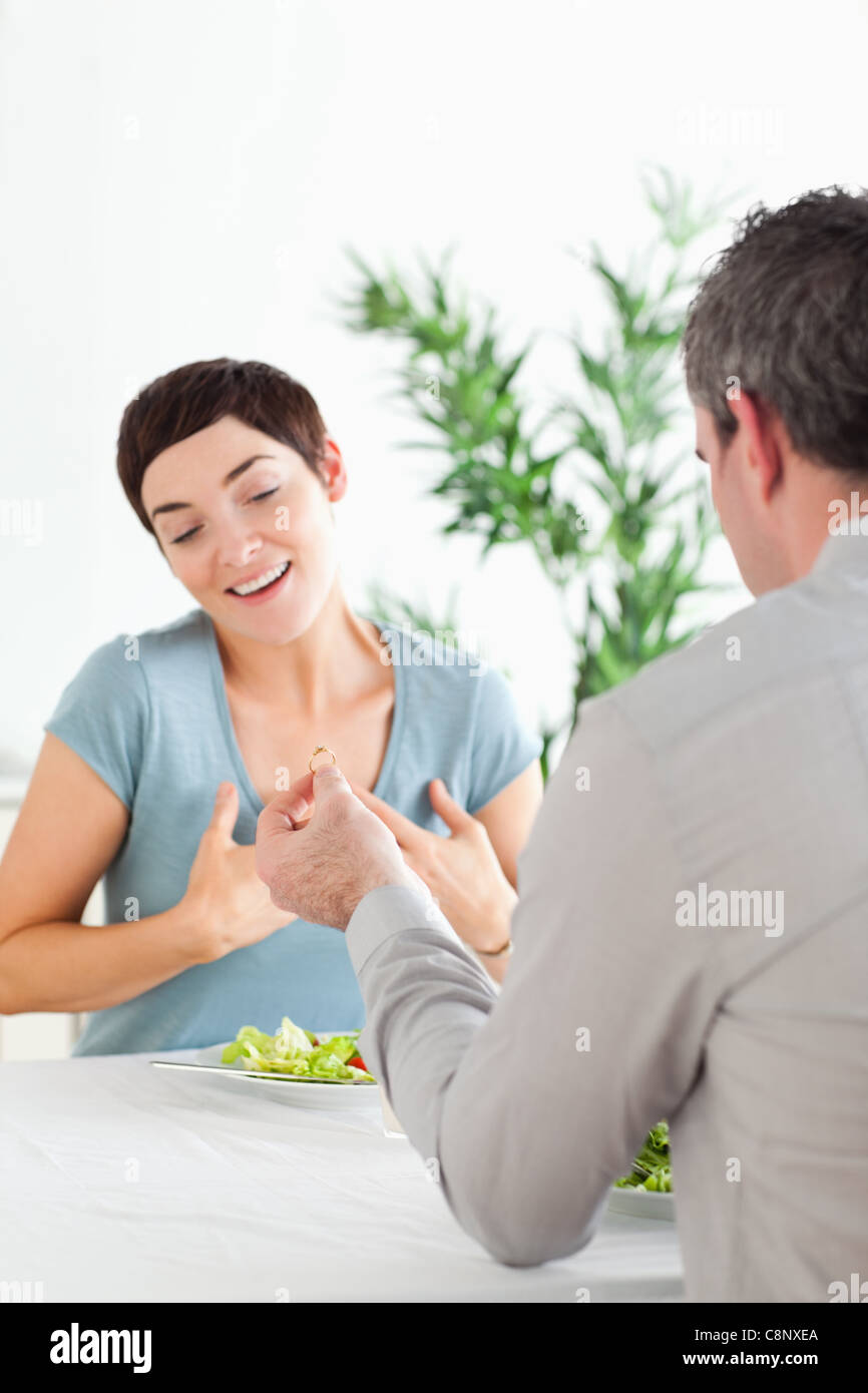 Man proposing to his amazed girlfriend during dinner - Stock Image