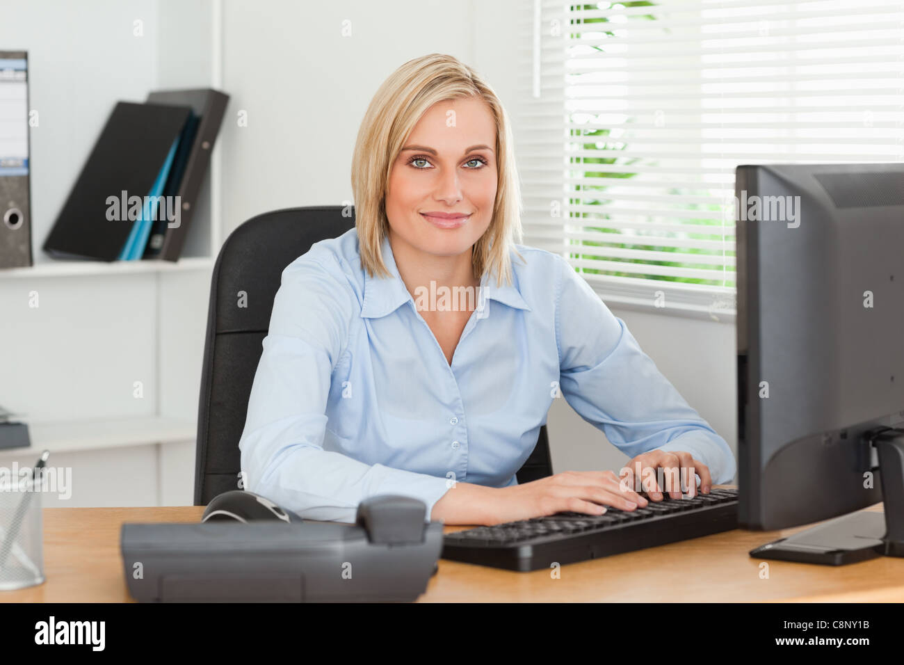 Working woman in front of a screen looks into camera Stock Photo