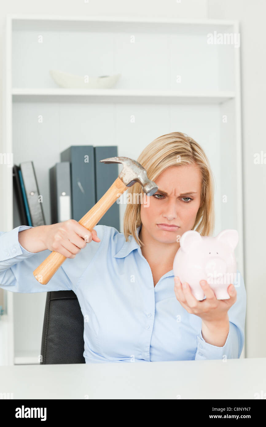 Angry woman wanting to destroy her piggy bank - Stock Image