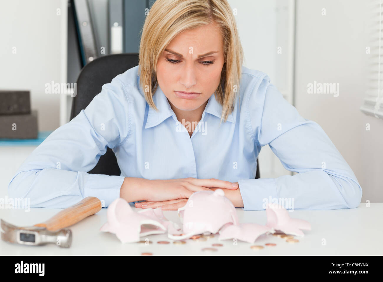 Sulking woman sitting in front of an shattered piggy bank with less in than expected - Stock Image