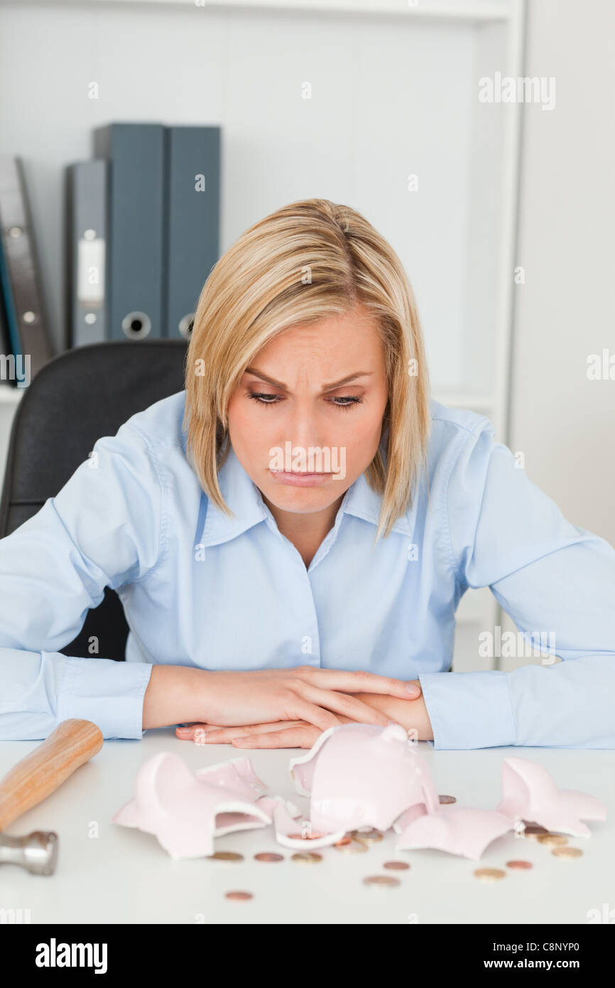 Sulking woman sitting in front of an shattered piggy bank - Stock Image