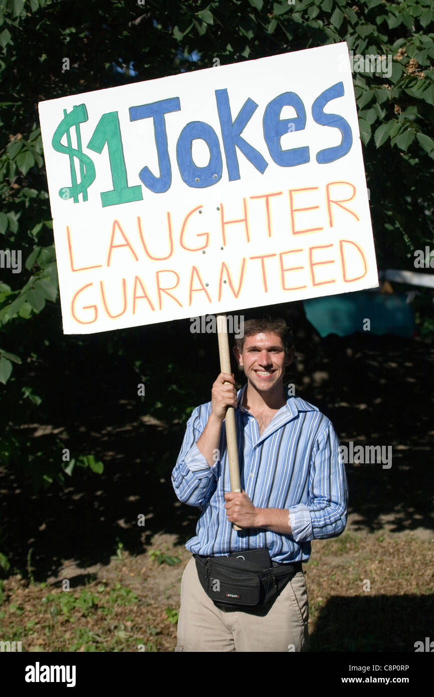 A man holds a sign offering jokes for a dollar a laugh while in Central Park. - Stock Image