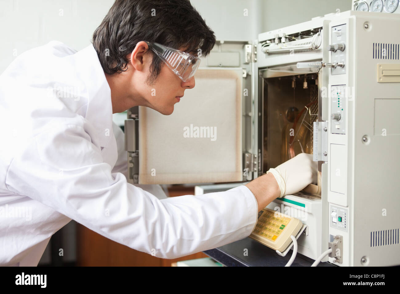 Male scientist using a laboratory chamber furnace - Stock Image