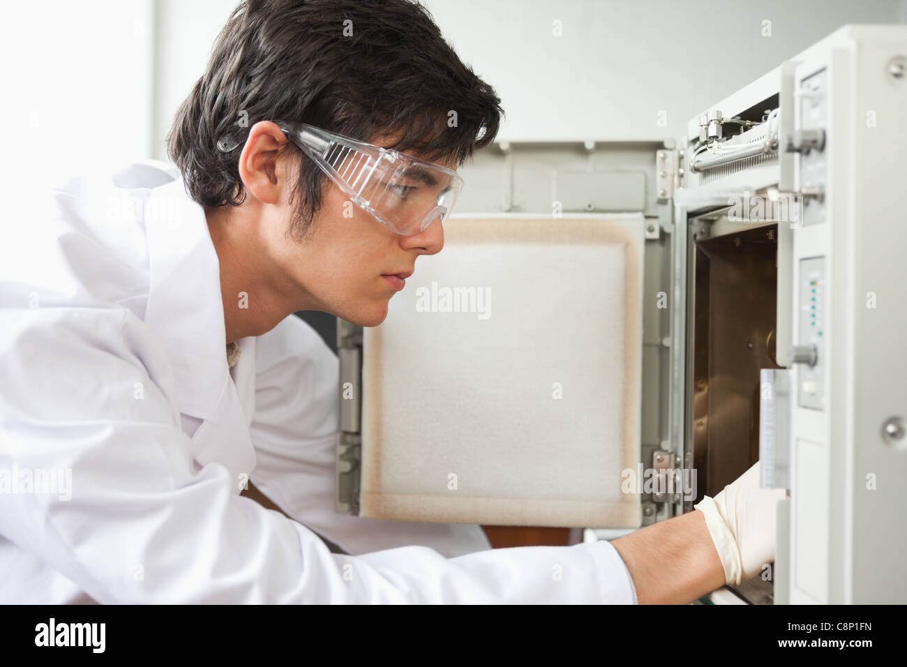 Close up of a scientist using a laboratory chamber furnace - Stock Image