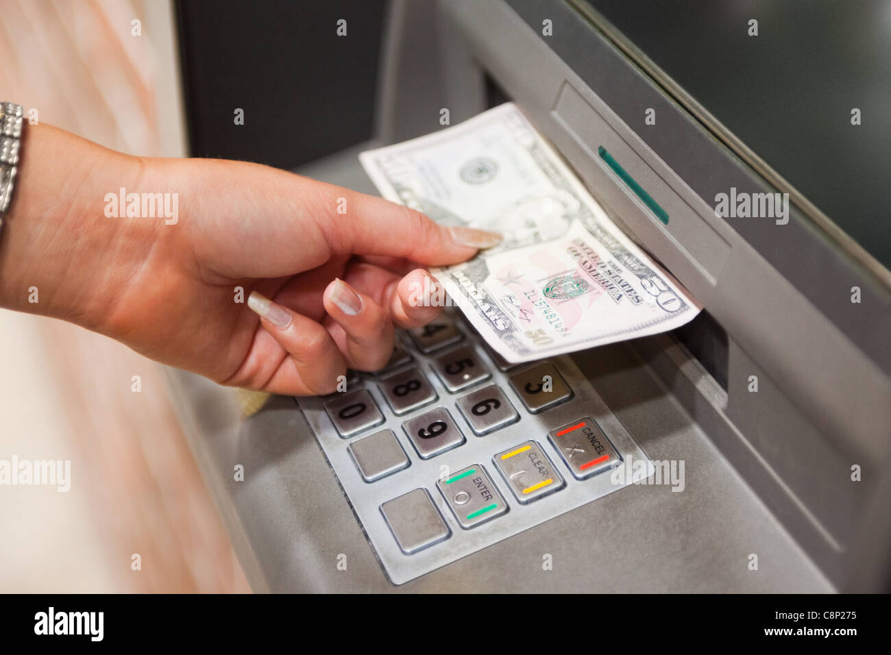 Feminine hand withdrawing dollars - Stock Image