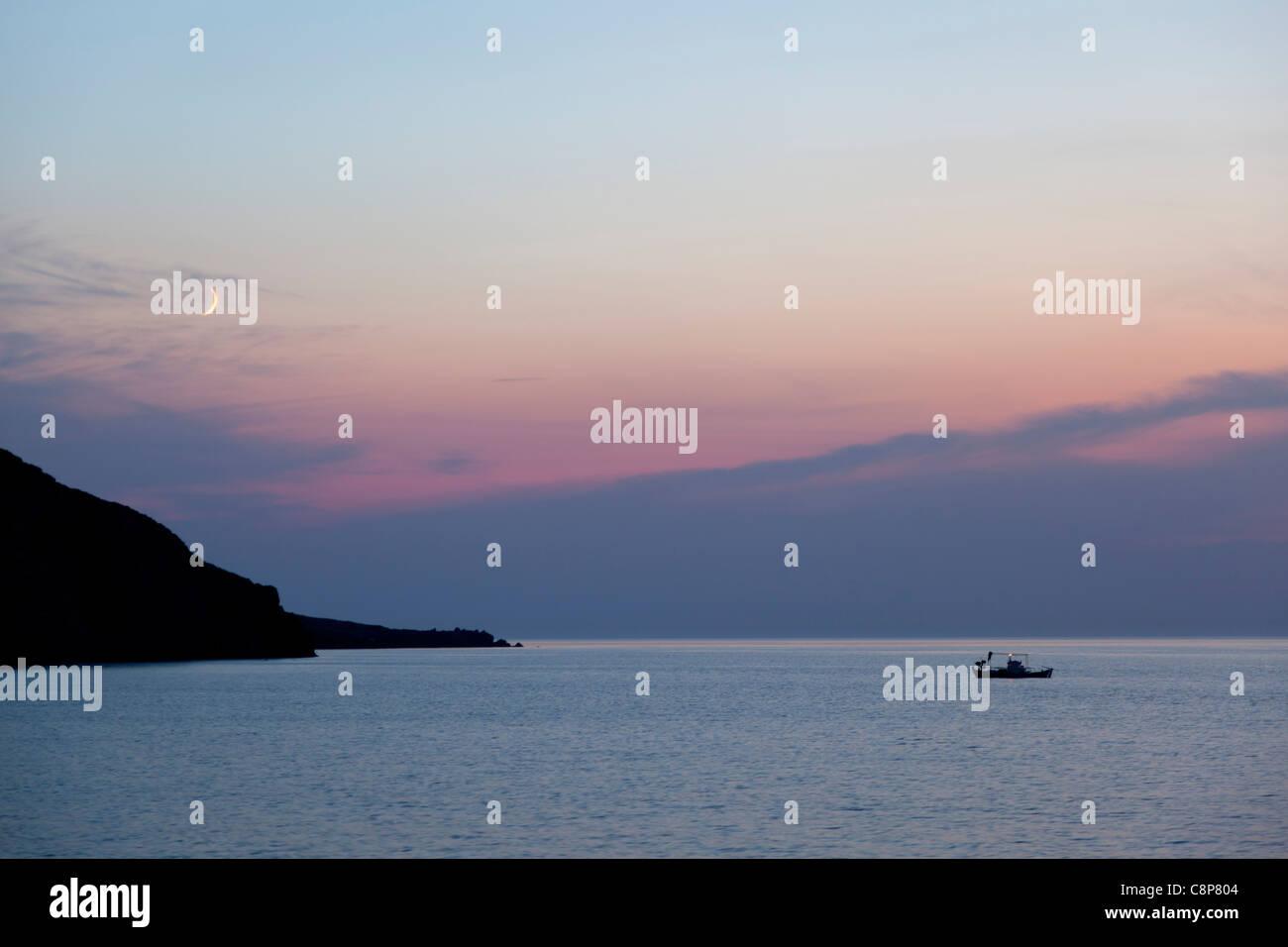 Fisher boat at sea near of Mithymna, Lesbos , Greece at sundown - Stock Image