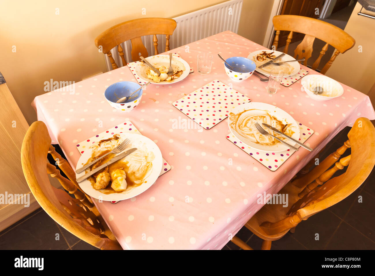 A family dinner table with dirty plates after a meal - Stock Image