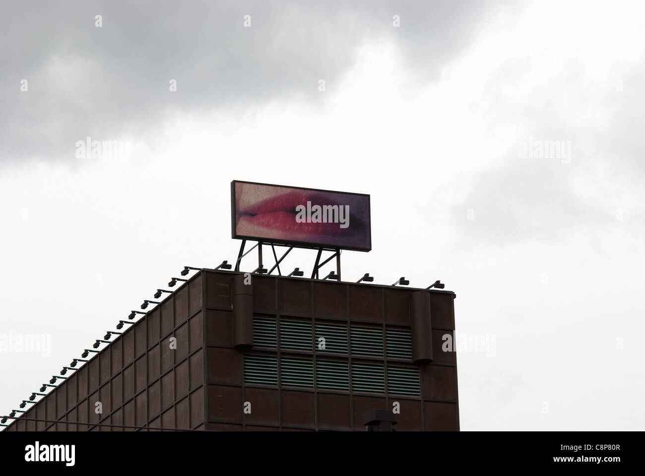 Funny billboard ads on top of building showing woman lips - Stock Image