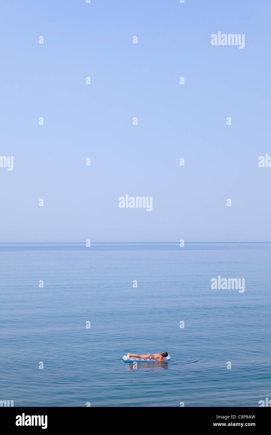 Floating on an air mattress in the blue sea - Stock Image