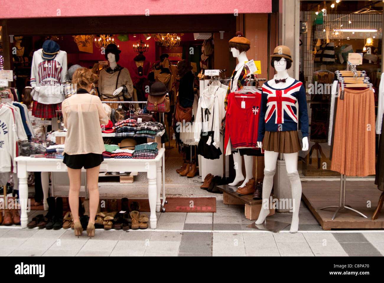 7d491b75556 A young shop assistant tending to a display at a womens fashion store,  Nagoya, Aichi, Japan