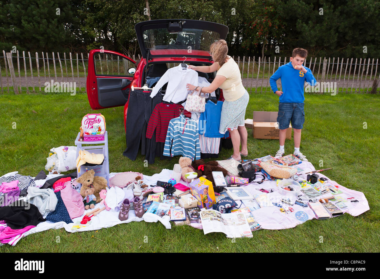 A family setting out their goods for sale at a car boot sale in Suffolk , England , Britain , Uk - Stock Image