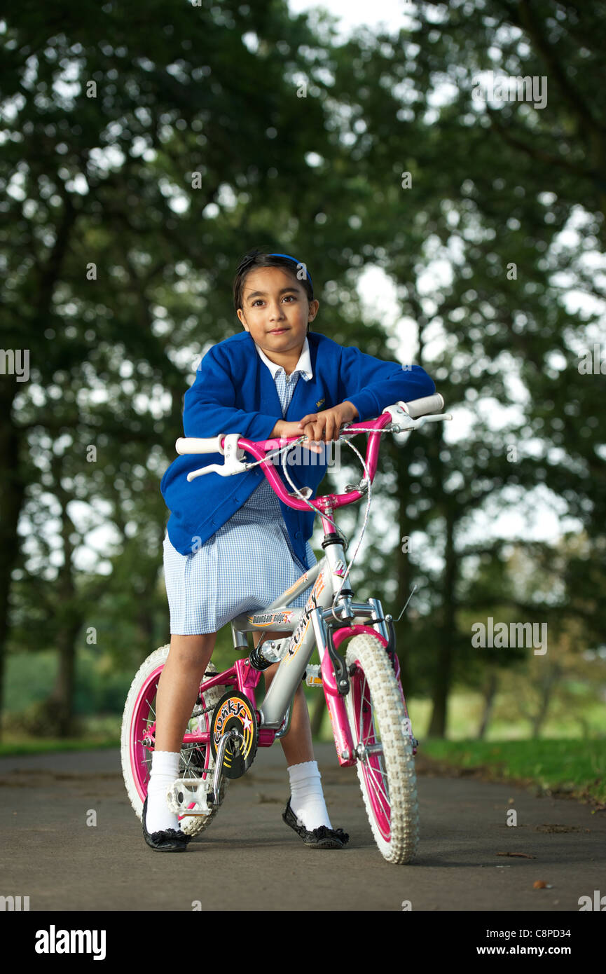 A young school girl cycling - Stock Image