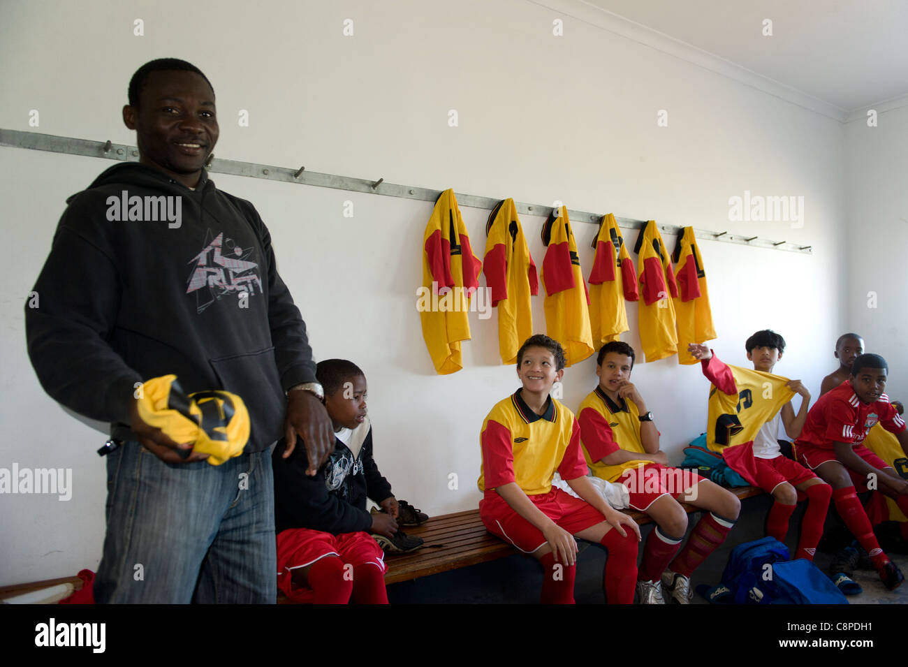 Football coach with junior team in the changing room Cape Town South Africa - Stock Image