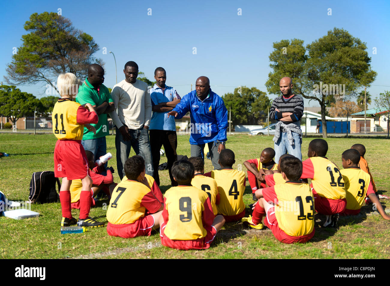 Football coach instructs junior team during half-time break Cape Town South Africa - Stock Image