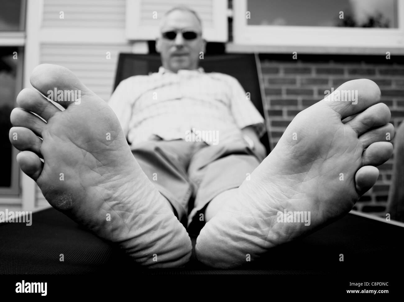 [Image: man-lying-down-in-chair-focus-on-feet-C8PDNC.jpg]