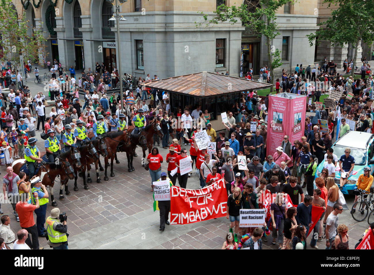 Protesters march past mounted police. The protest was held to coincide with the start of CHOGM 2011 held in Perth. - Stock Image