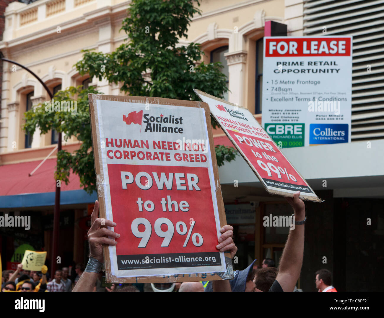 Socialist Alliance protesters hold  'Human Need Not Corporate Greed' & 'Power to the 99%' placards - Stock Image