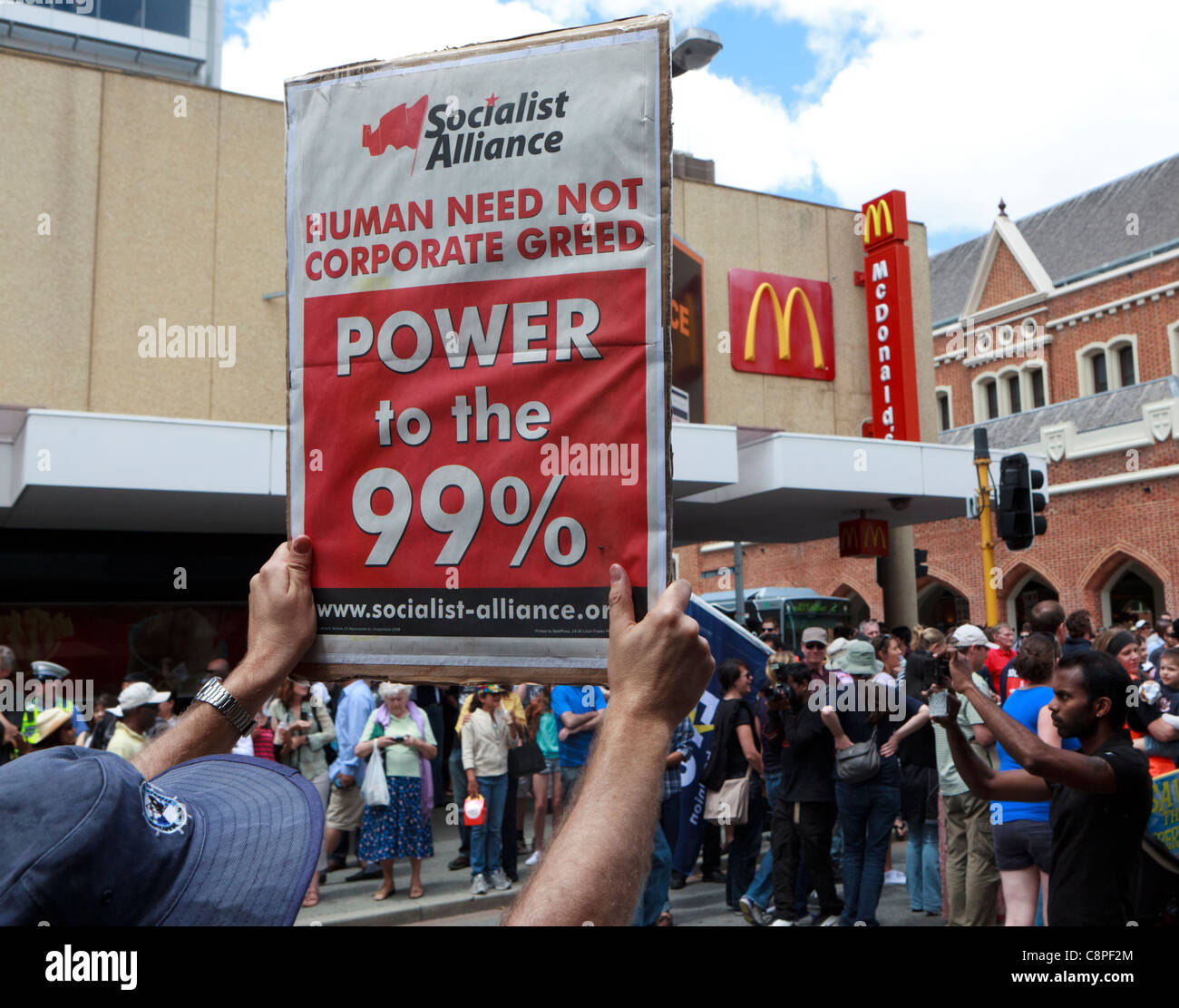 Protester holds a 'Human Need Not Corporate Greed' Banner next to a Macdonald's sign. - Stock Image