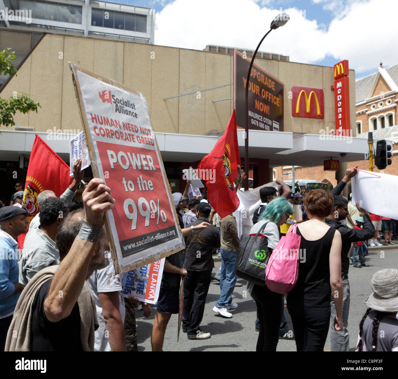 Protester holds a 'Human Need Not Corporate Greed' Banner near a Macdonald's sign. - Stock Image