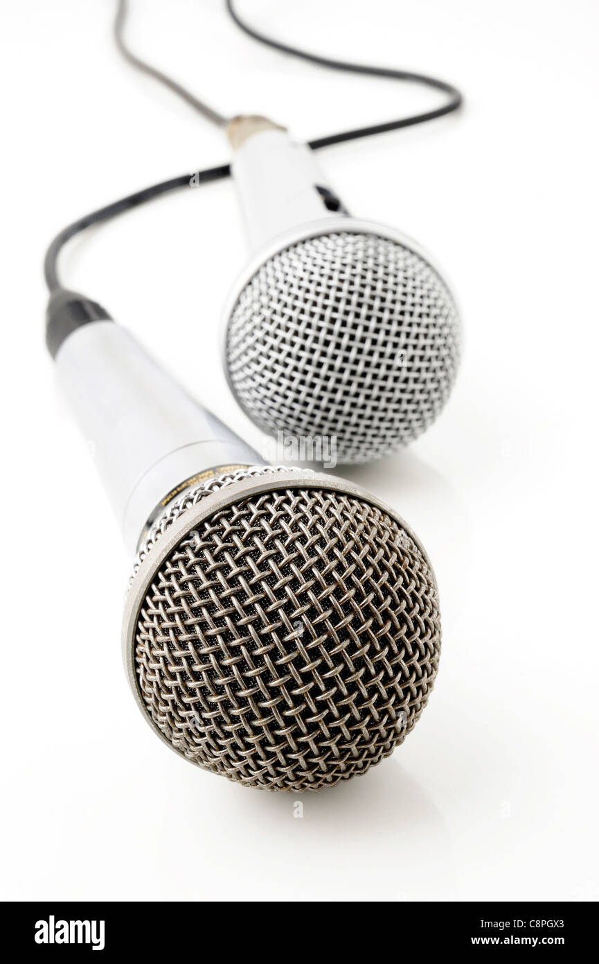 Silver microphone with black wire on white - Stock Image