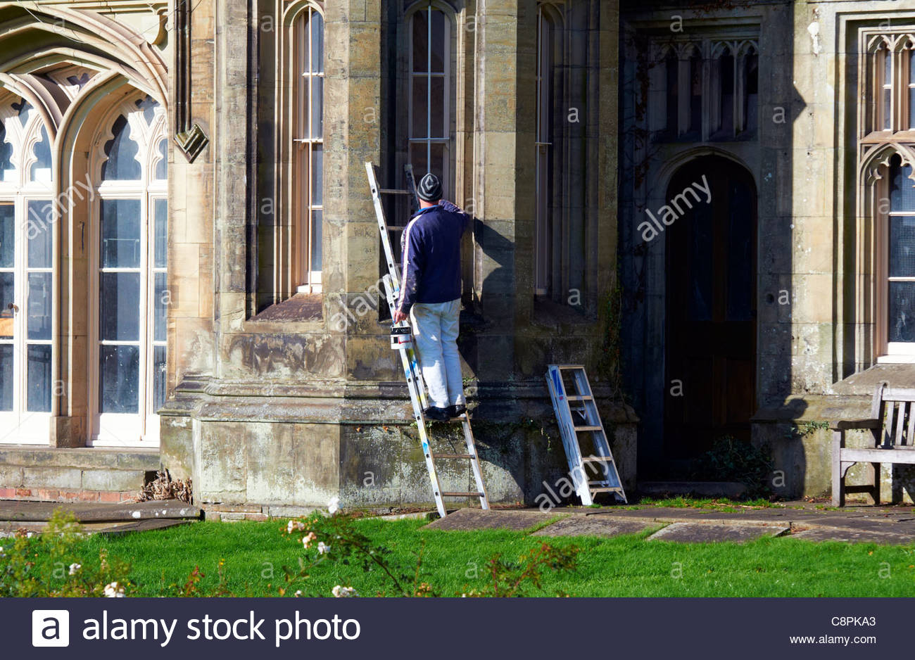 painter and decorator painting bay windows in margam country park near port talbot south wales - Stock Image