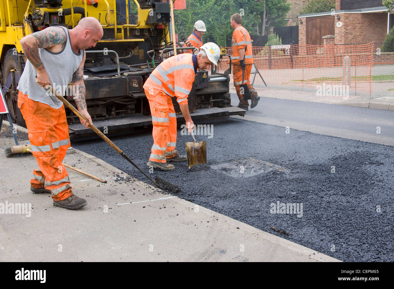 Workmen  cleaning surface of manhole cover and leveling tarmac, using shovel and rake, after road surface has been - Stock Image