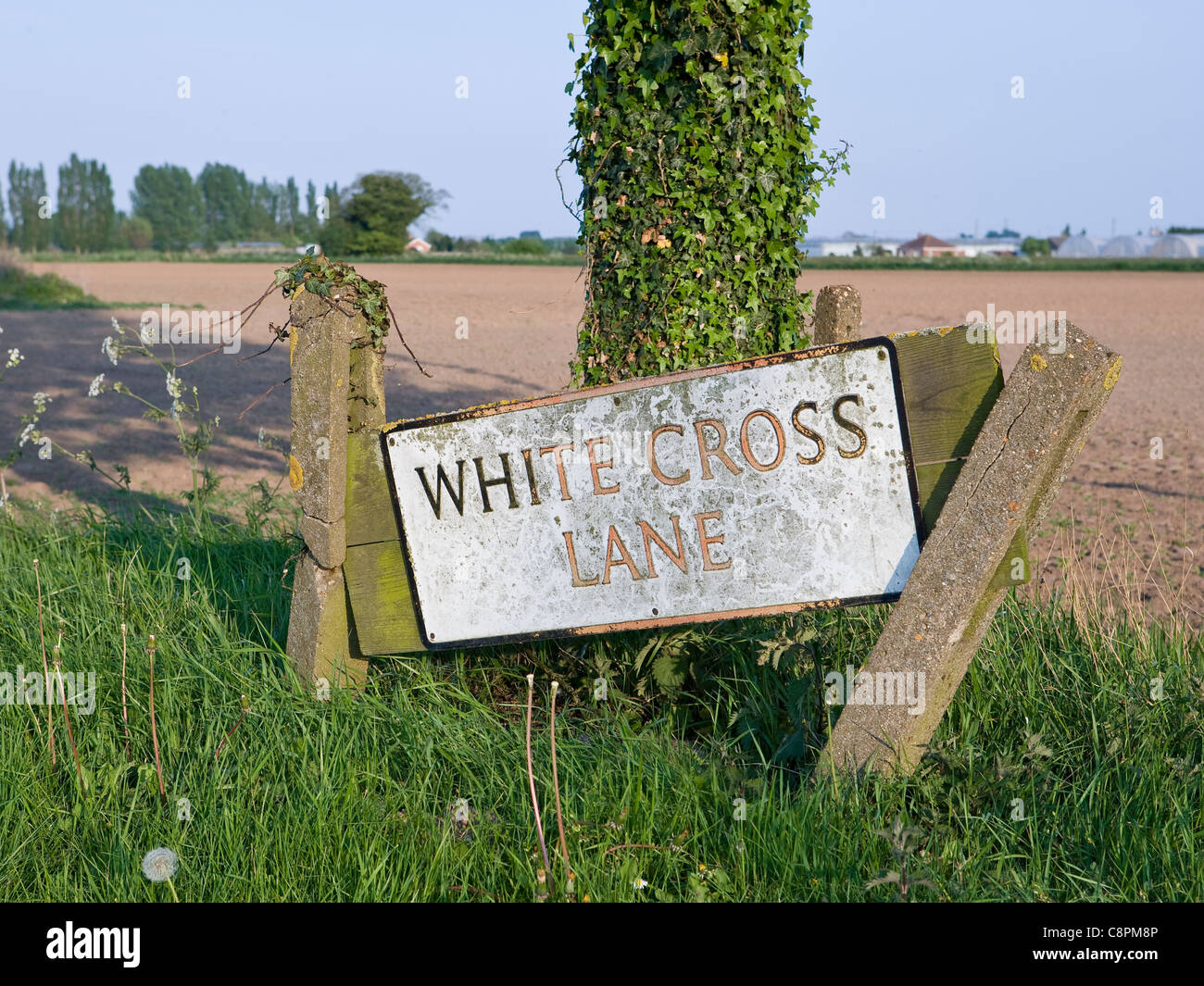 A neglected name board at beginning of a country lane. - Stock Image