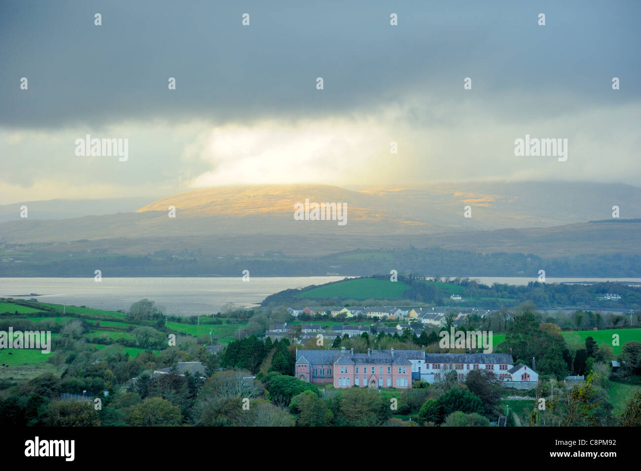 A break in the clouds over the Caha mountains from Bantry on a dull day - Stock Image