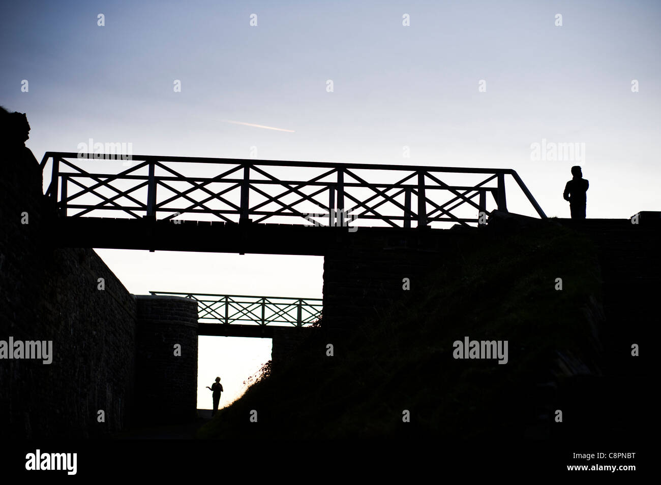 Two separate people standing, and footbridges, silhouetted at dusk, UK - Stock Image