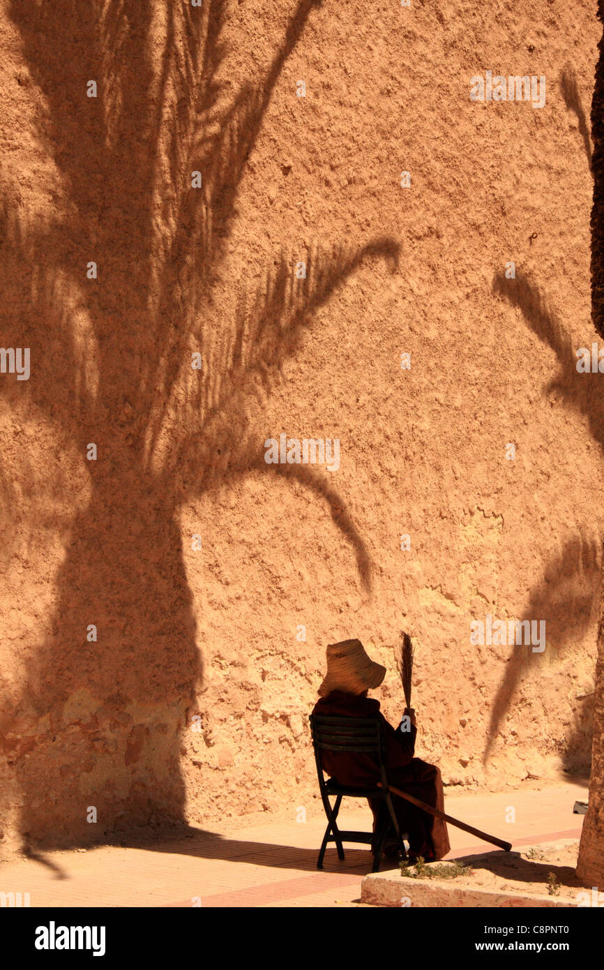Elderly lady fans herself in the shade of a palm tree by the town walls that encircle the medina in Essaouira, Morocco, - Stock Image