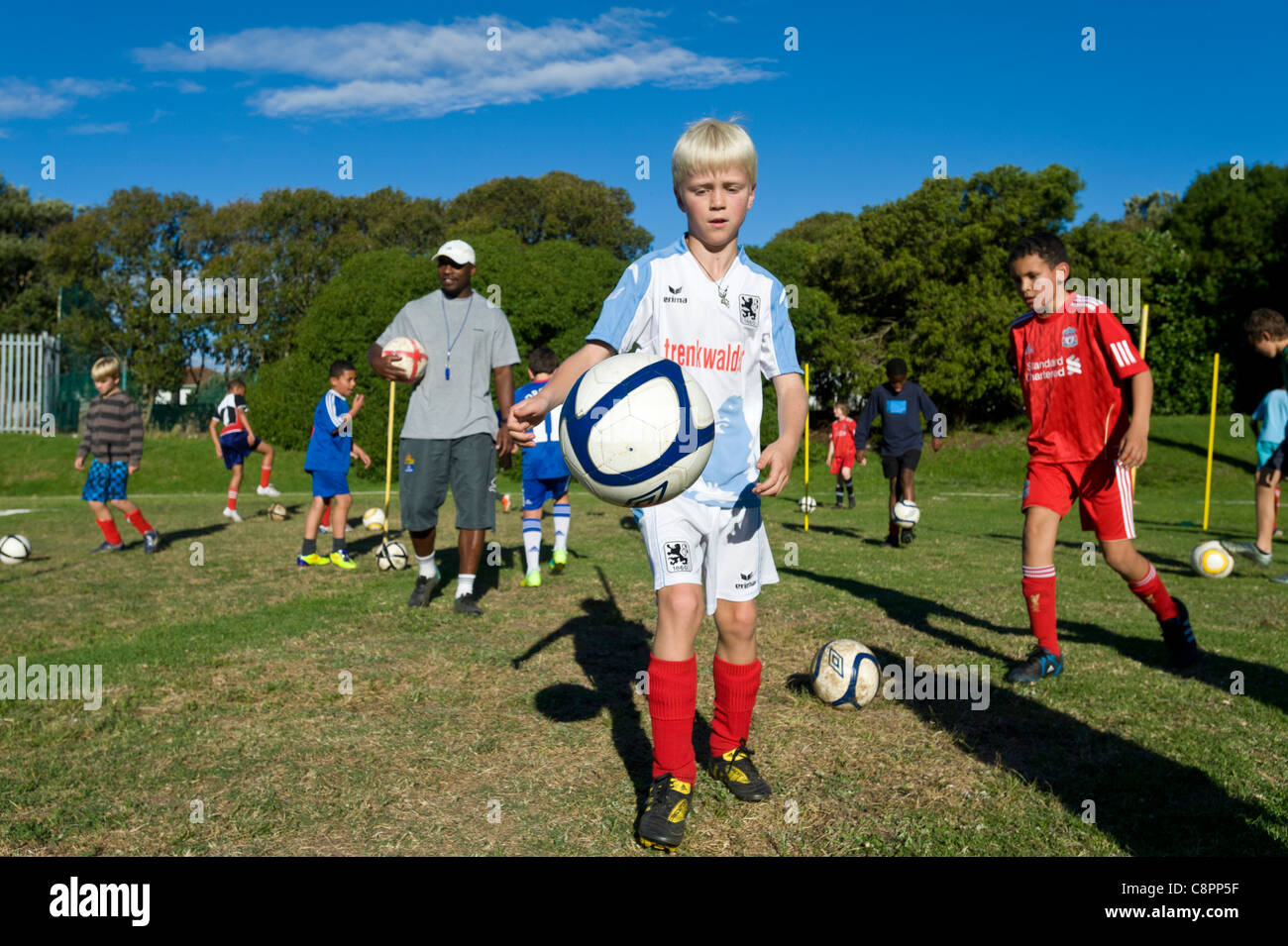 Football coach watching junior players practicing ball skills Cape Town South Africa - Stock Image