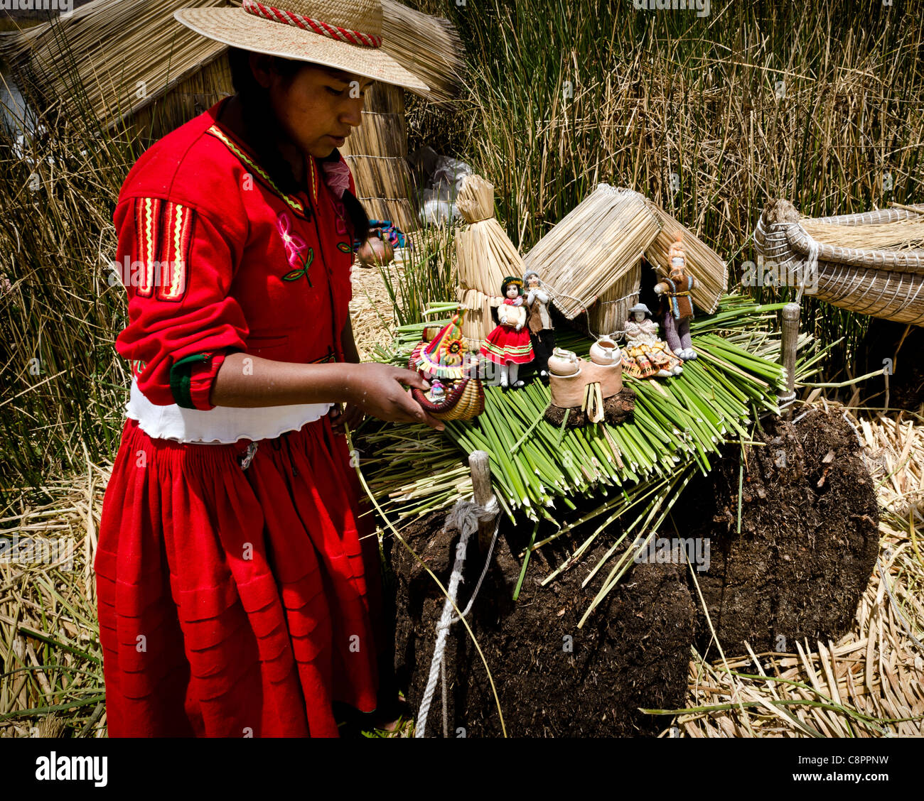 Woman wearing a traditional costume selling handcrafts Uros islands Titicaca lake Puno region Peru - Stock Image