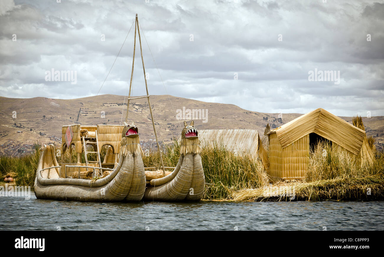 Houses and boat made of reeds Uros Islands Titicaca lake Puno region Peru - Stock Image