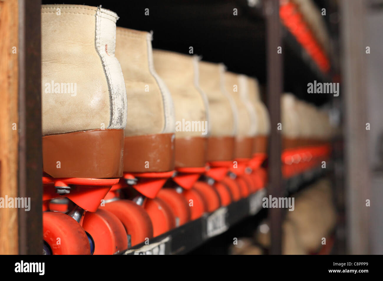 Roller skates at a rental facility lined up by size in a rack - Stock Image