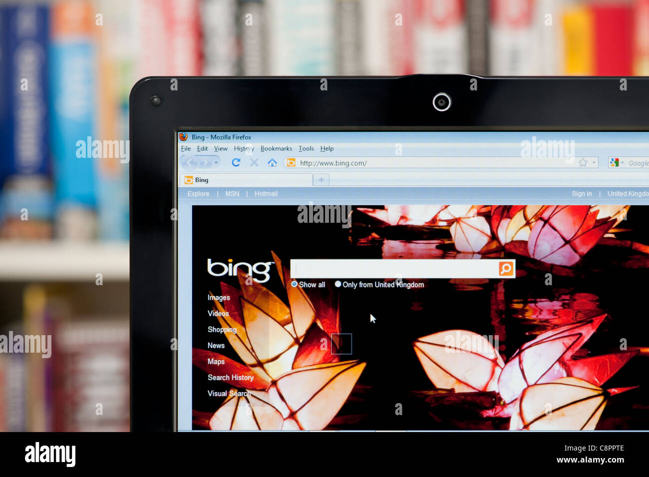 The Bing website shot against a bookcase background (Editorial use only: print, TV, e-book and editorial website). - Stock Image