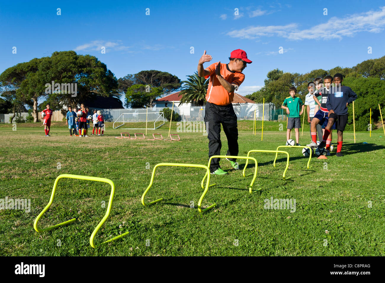 Football coach instructing junior players practicing skills Cape Town South Africa - Stock Image