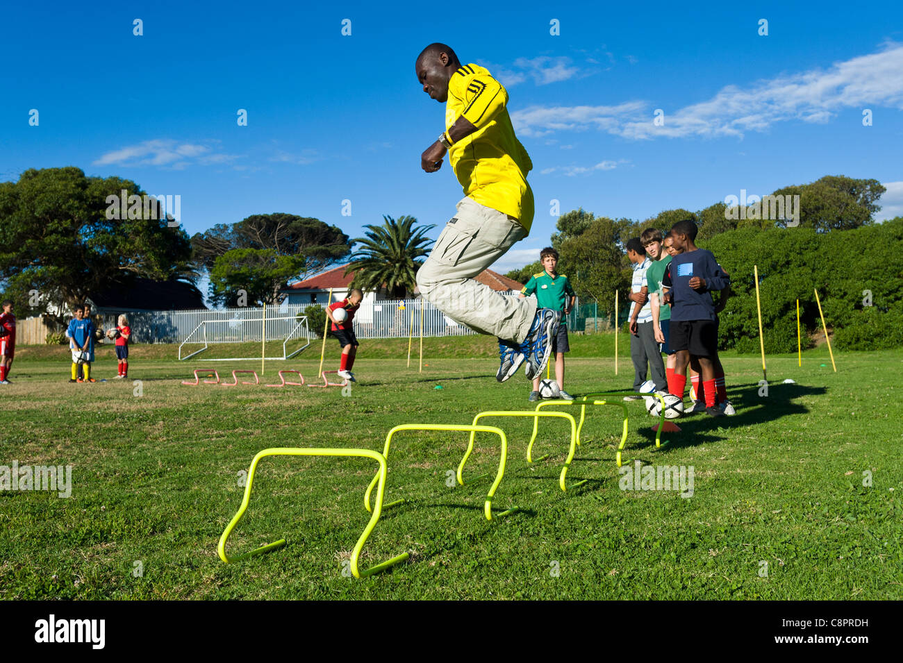 Football coach showing junior players practicing skills Cape Town South Africa - Stock Image