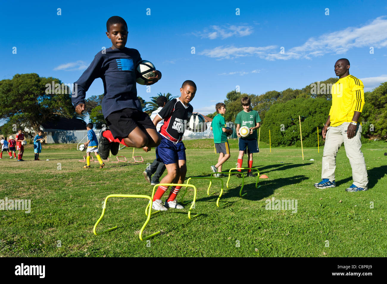 Football coach watching junior players practicing skills Cape Town South Africa - Stock Image