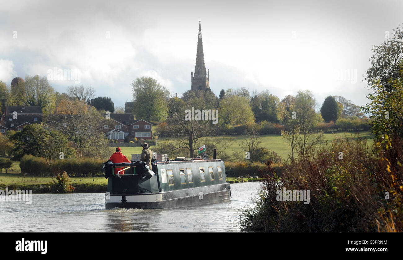 NARROWBOAT BARGE ON CANAL WITH COUNTRYSIDE AND CHURCH SPIRE RE BOATING HOLIDAYS RETIREMENT RELAXING LIFESTYLE ETC - Stock Image