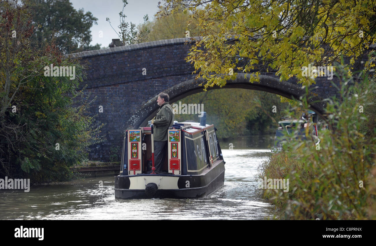 MAN ON NARROWBOAT BARGE ON CANAL WITH BRIDGE RE BOAT HOLIDAYS RELAXING RETIREMENT LIFESTYLE WATERWAYS ETC UK - Stock Image