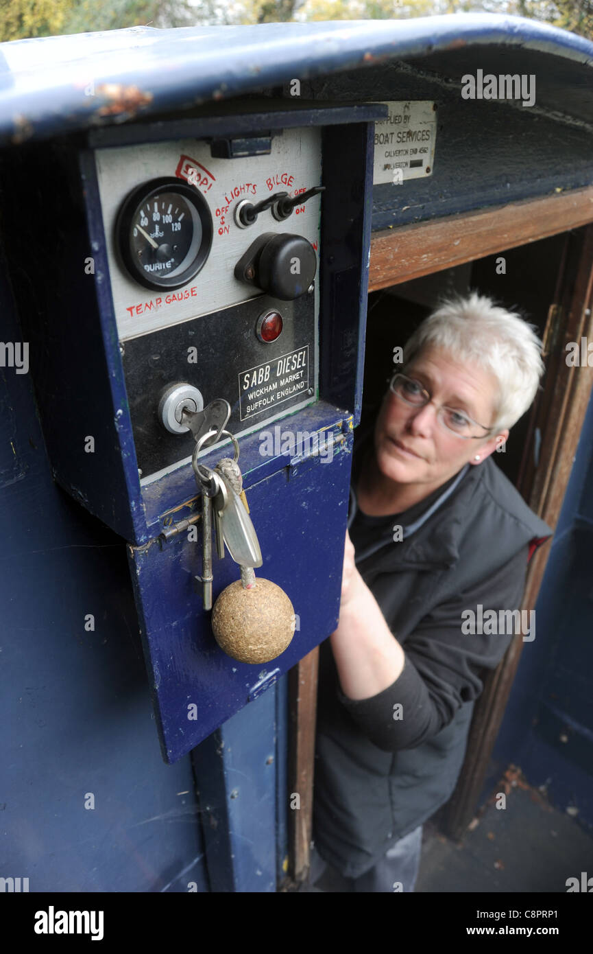 WOMAN LOOKING AT CONTROL SWITCHES ON CANAL BARGE NARROWBOAT RE BILGE PUMP STARTER SWITCH IGNITION CONTROL PANEL - Stock Image