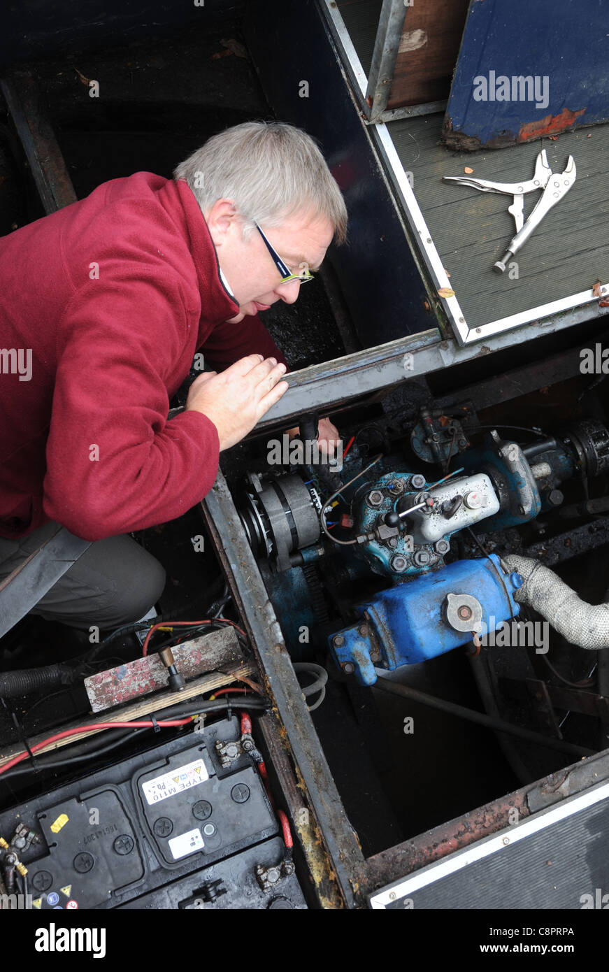 MAN WORKING ON CANAL BOAT NARROWBOAT BARGE DIESEL ENGINE WITH TOOLS RE BOATING MAINTENANCE HOLIDAY BREAKDOWNS ETC - Stock Image