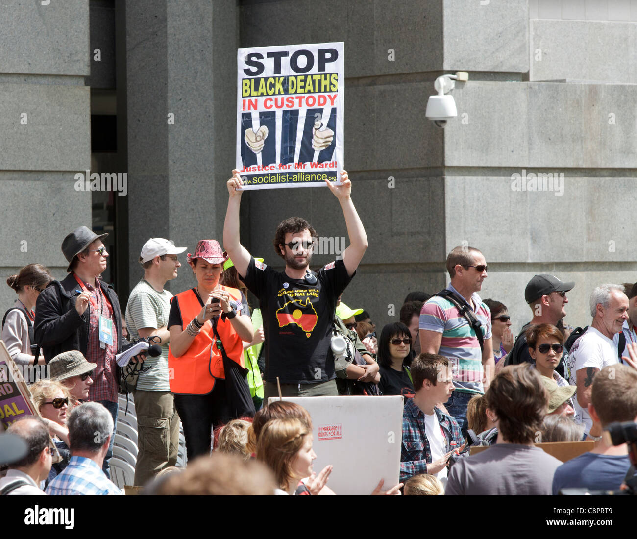 Protester holding a 'Stop Black Deaths in Custody' placard protesting about Aboriginal deaths in custody. - Stock Image